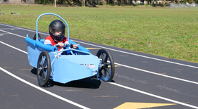 Student races the car he built in the Engineering Magnet program.