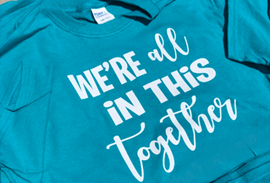 A blue T-shirt that says: We're all in this together
